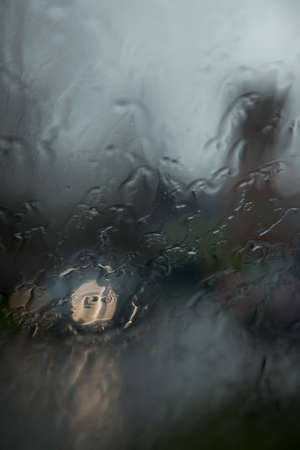 lonliness: car lights and reflection seen through wet windshield during rainfall