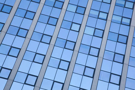 repetitious: abstract pattern of blue squares on facade of office building Stock Photo