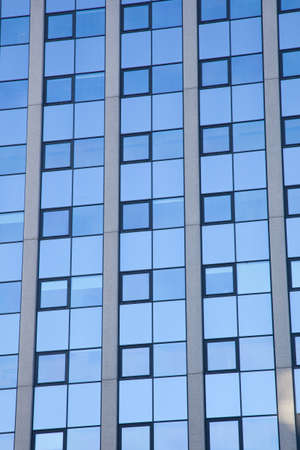 abstract pattern of blue squares on facade of office building and reflections Stock Photo