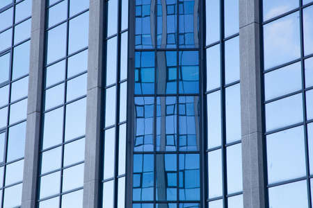 repetitious: abstract pattern of blue squares on facade of office building and reflections Stock Photo