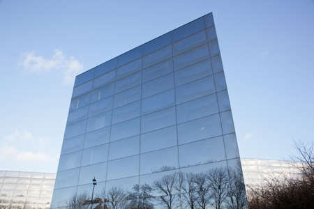 part of geometrically shaped modern glass building with reflections of blue sky and winter tree