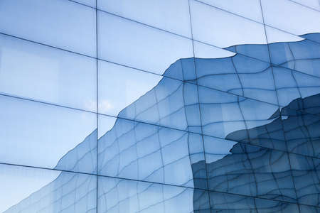 part of geometrically shaped modern glass building with reflections of blue sky and glass wall