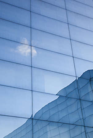 part of facade of geometrically shaped modern glass building with reflections of blue sky and glass wall
