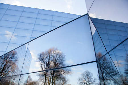 glass facade of modern office building with reflections of trees and blue sky Reklamní fotografie