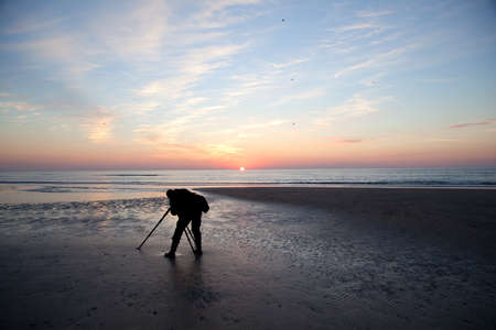 man with camera on tripod alone on beach at sundown on the North Sea cost of the netherlands