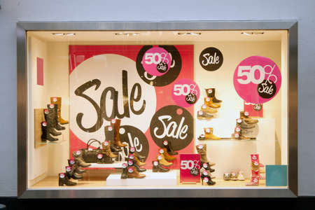 sale signs in shop window of shoe shop