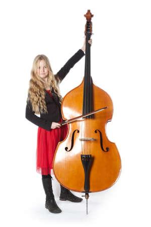 赤いドレスの若いブロンドの女の子は白い背景スタジオでコントラバスを果たしています。