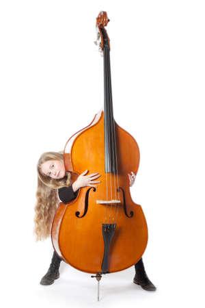 jong blond meisje kijkt van achter contrabas in de studio tegen een witte achtergrond