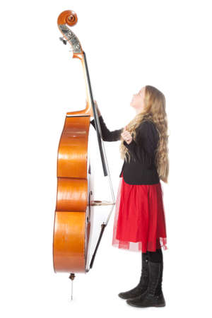 young blond girl in red dress looks up to double bass in studio against white background