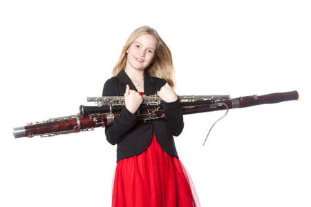 young blond girl holds woodwind instruments in studio against white background Reklamní fotografie - 35692849