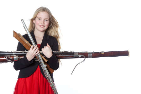 young blond girl holds woodwind instruments in studio against white background Archivio Fotografico