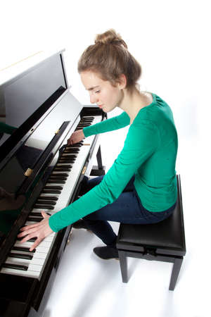 teenage girl plays piano in studio wearing green shirt and jeans