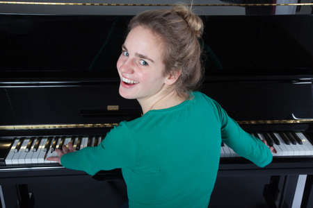 teenage girl plays piano in green shirt and smiles