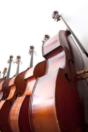 upright row: row of double basses leaning against a wall Stock Photo