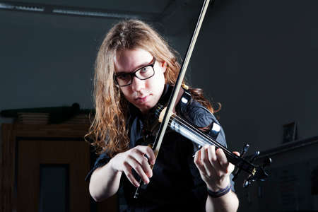 harsh light: young man with long hair and glasses plays electric violin with harsh light