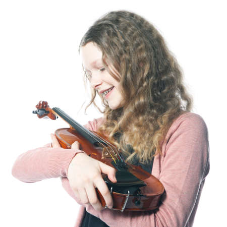 young girl with blond curly hair holds violin in studio with white background photo