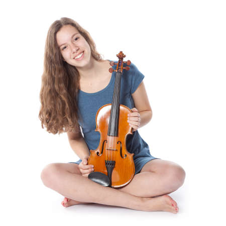 teenage girl in minidress sits with violin in studio photo