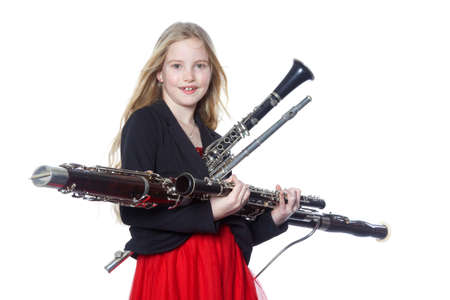 woodwind: young blond girl holds woodwind instruments in studio against white background Stock Photo