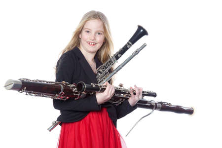 young blond girl holds woodwind instruments in studio against white background Standard-Bild