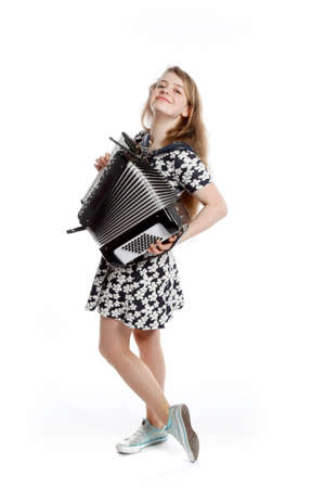 teenage girl stands in studio with accordion against white background Stock Photo
