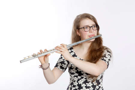 teenage girl plays the flute against white background