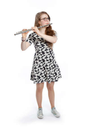 眼鏡とブロンドの 10 代の少女は白い背景がフルートを吹く