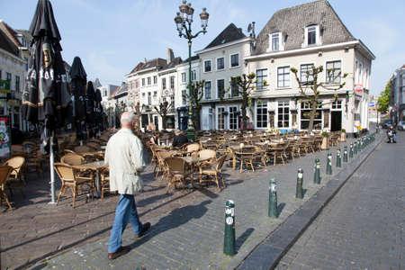 breda: man walks on havermarkt in Breda on spring morning in the netherlands Editorial