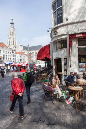 breda: people enjoying a drink on the market near breda cathedral in the netherlands