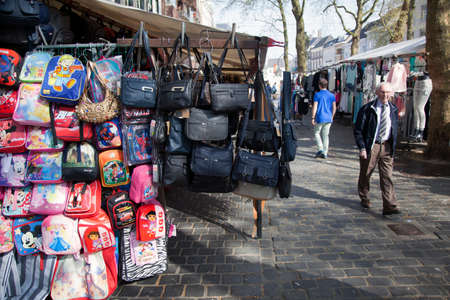 breda: bags hang from market stall in the dutch city of breda on sunny spring day Editorial
