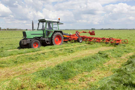 turner: Red hay turner behind tractor in green meadow in the netherlands Stock Photo