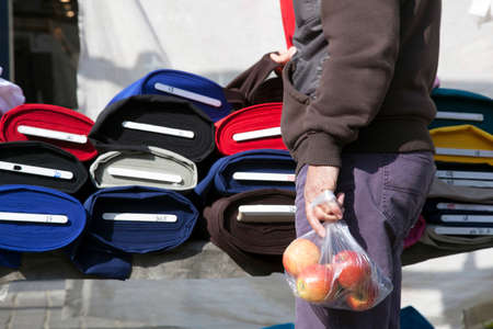 breda: Person holding bag of apples while testing fabric on market