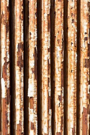 old central heating radiator with cracked white paint and rust