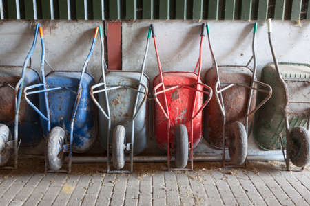 Six old and rusty wheelbarrows rest against wall of farm barn