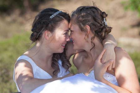 lesbianas: dos novias sonríen y se abrazan en un entorno de naturaleza en día soleado Foto de archivo