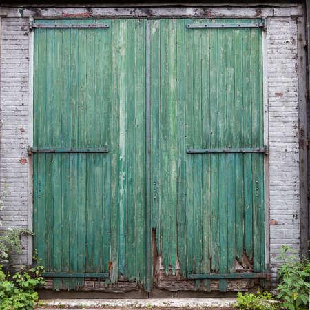 puertas de madera: grandes puertas de granero viejo con la pintura descascarada verde en la pared de ladrillo blanco Foto de archivo