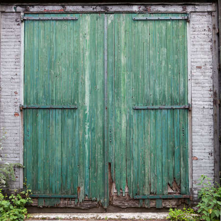 large doors: large old barn doors with peeling green paint in white brick wall