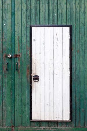 small white door in large green barn door with peeling green paint Standard-Bild