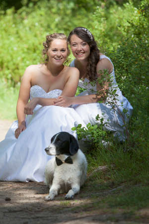 just married lesbian pair in white wedding dresses and their dog in forest Foto de archivo