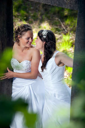 romantic picture of two smiling brides in nature surroundings