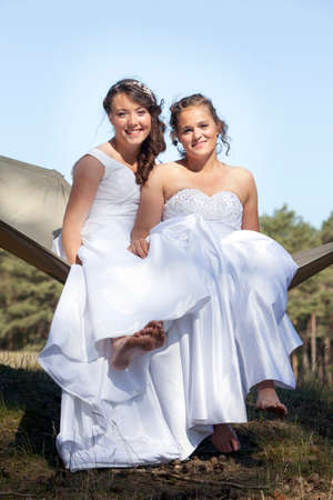 two brides relax smiling in hammock against blue sky with forest background Banque d'images