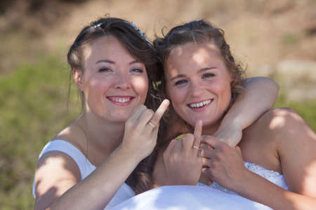 homosexual partners: two brides smile and show their wedding rings in nature surroundings on sunny day