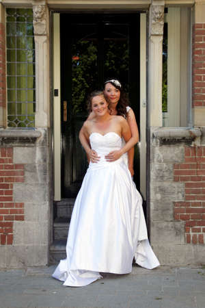 just married lesbian pair holds each other on doorstep of old city hall Reklamní fotografie