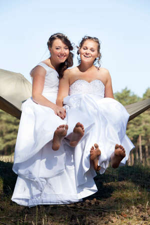 lesbian love: two brides show bare feet in hammock against blue sky with forest background