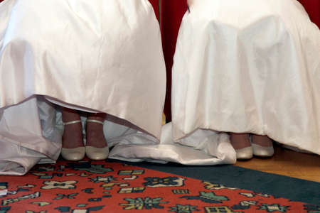 shoes and white dresses of two brides sitting next to each other