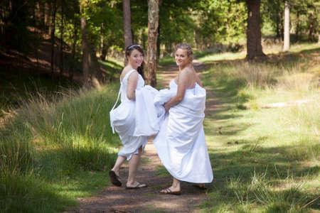 twee bruiden lopen op bosweg met rokken in hun armen, terwijl terug te kijken glimlachend
