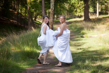 two brides walk on forest path with skirts in their arms while looking back smiling Reklamní fotografie - 41930070