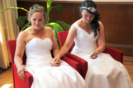 結婚 2 つの花嫁は赤い椅子に座って手をつないでください。
