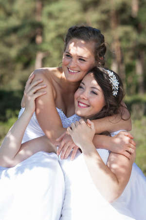 two brides smile and embrace in nature surroundings on sunny day Stock Photo