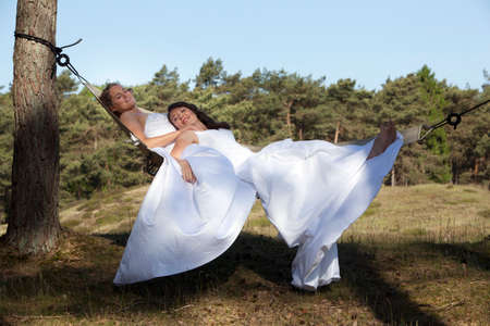 two brides relax in hammock against blue sky with forest background