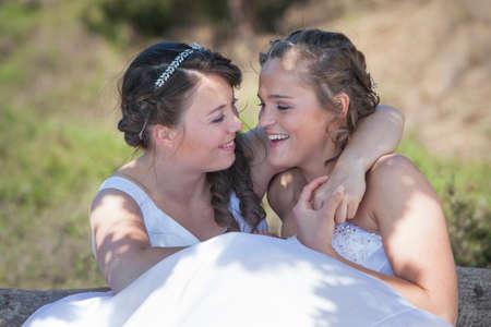 2 つの花嫁の笑顔と抱擁晴れた日に自然環境の中で